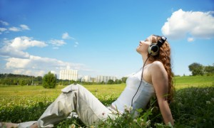 women with headphones on grass